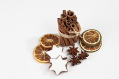 Bundle of cinnamon sticks staranises dried orange slices christmas pastries on white background Stock Image