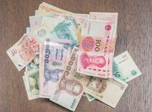 A bundle of different Asian money lying on the wooden table. Concept of global world variety. Asian travel concept. Exchange concept Royalty Free Stock Images