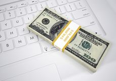 Bundle of dollar bills lying on computer keyboard. Bundle of dollar bills lying on a computer keyboard. View from above Stock Images