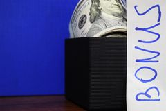Bundle of dollars in gift box isolated on blue background, the inscription Bonus royalty free stock photo