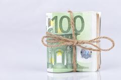 A bundle of euro bills tied with a rope and placed on white. Background Royalty Free Stock Photos
