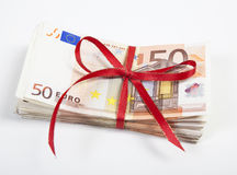 A bundle of euro bills. Wrapped with a red ribbon. white background stock photos