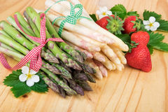 Bundle of fresh asparagus with strawberries on wood. Royalty Free Stock Photo