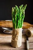 Bundle of fresh green asparagus wrapped in craft paper tied with twine standing on wood kitchen table Stock Photo
