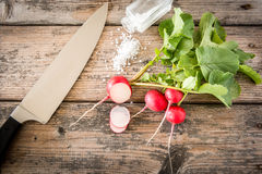 Bundle of fresh radishes on wooden table Stock Photos
