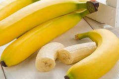 Bundle of fresh, ripe, yellow bananas with sliced banana pieces Stock Photo