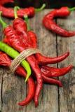 Bundle of hot sorts of pepper. On wooden desk stock image