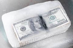 Bundle of hundred-dollar bills frozen in ice.  Royalty Free Stock Image