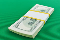 Bundle of hundred dollar bills. On green background Royalty Free Stock Photo