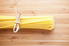 Bundle of Italian spaghetti pasta tied with string lying on old Royalty Free Stock Image