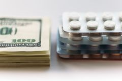 Bundle of money and  pack of medication tablets or drug pills, close-up. Expensive health care concept Royalty Free Stock Images