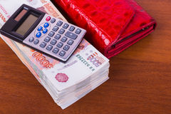 A bundle of money, red leather wallet and calculator are on the table Royalty Free Stock Image