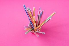 A bundle of multi-colored drinking straws in a paper Cup. On a pink background. fashion minimal. flat lay Stock Photography