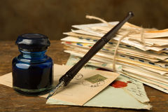 Bundle of old letters and ink well. Vintage ink well and fountain pen on a table with old letters Royalty Free Stock Image