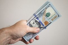 Bundle of One Hundred Dollars notes in male hand Stock Photography