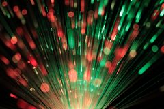 Bundle of optic fibers in red and green light stock image