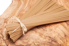 Bundle of Organic uncooked Brown Rice Spaghetti pasta tied with straw on a natural olive wood cutting board . Gluten-free and sodium-free alternative to stock images