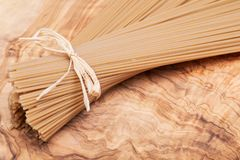 Bundle of Organic uncooked Brown Rice Spaghetti pasta tied with straw on a natural olive wood cutting board . Gluten-free and sodium-free alternative to stock photos