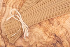 Bundle of Organic uncooked Brown Rice Spaghetti pasta tied with straw on a natural olive wood cutting board . Gluten-free and sodium-free alternative to royalty free stock image