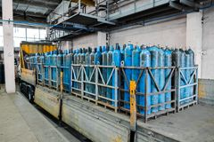 A bundle of oxygen cylinders with compressed gas secured on yellow skids in platform.Oxygen tanks. Liquefied oxygen production. Empty flasks. Laboratory stock photos