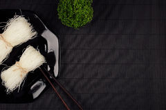 Bundle raw asian noodles in plate with chopsticks on black striped mat background with copy space, top view. Restaurant menu mock up Royalty Free Stock Photo