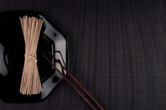 Bundle raw asian noodles in plate with chopsticks on black striped mat background with copy space, top view. Restaurant menu mock up Royalty Free Stock Photos
