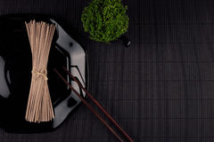 Bundle raw asian noodles in plate with chopsticks, green plant on black striped mat background with copy space, top view. Modern minimalistic style restaurant Royalty Free Stock Images