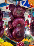 Bundle of red Crimean onion hanging over the counter market Royalty Free Stock Photos
