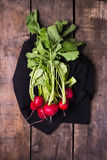 Bundle of red radishes on rustic board Stock Photos
