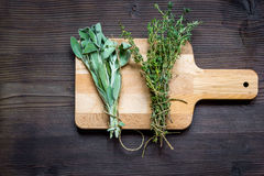 Bundle of sage and thyme on wooden board top view Royalty Free Stock Photos