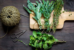 Bundle of sage and thyme on wooden board top view Royalty Free Stock Photography