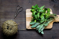 Bundle of sage and thyme on wooden board top view Royalty Free Stock Photo