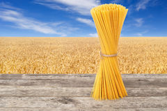 Bundle of uncooked spaghetti. From durum wheat on table with ripe cereal field on the background.  Golden wheat field with blue sky. Healthy eating. Photo with Stock Photos