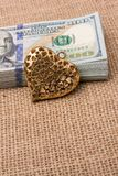 Bundle of US dollar and a heart shape. Heart icon bundle of US dollar placed on a linen canvas Royalty Free Stock Images