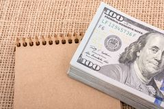 Bundle of US dollar on a notebook Stock Images
