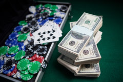 Bundle of US dollars, playing cards and casino chips on poker table Royalty Free Stock Image