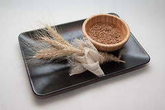 Bundle of wheat on black plate Royalty Free Stock Photo