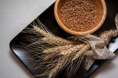 Bundle of wheat on black plate Royalty Free Stock Image