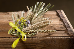 Bundle of wheat with flower and band. Ojn the wooden desk Stock Photo