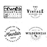Bundle of wilderness badges, logos, design elements. Mountain shapes, arrows, deer antlers. Vintage retro styled stock vector illustration Royalty Free Stock Photo