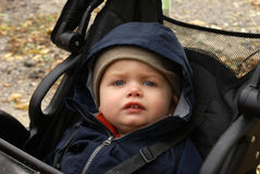 Bundled Baby Boy. A cute baby boy is all bundled up during his stroll in the colder northern autumn weather royalty free stock photos