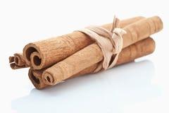 Bundled cinnamon sticks on white background Royalty Free Stock Photography