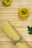 Bundled dried tagliatelle pasta. On wooden table Royalty Free Stock Photography