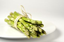 Bundled green asparagus on a plate Royalty Free Stock Images