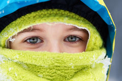 Bundled up blue eyed kid. Closeup of bundled up blue eyed little boy with snow flakes details stock images