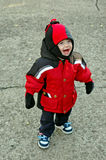 Bundled up happy child. Image of a happy child outdoors wearing a winter coat and cap stock photo