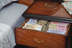 Bundles of banknotes in bedside table Royalty Free Stock Photo