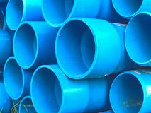 Bundles of blue plastic pipes for water transport. Pipe batch. Construction site royalty free stock images