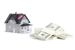Bundles of dollars in front of home. Real estate concept - bundles of dollars in front of home architectural model Royalty Free Stock Photo