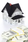 Bundles of dollars in front of house model Royalty Free Stock Image